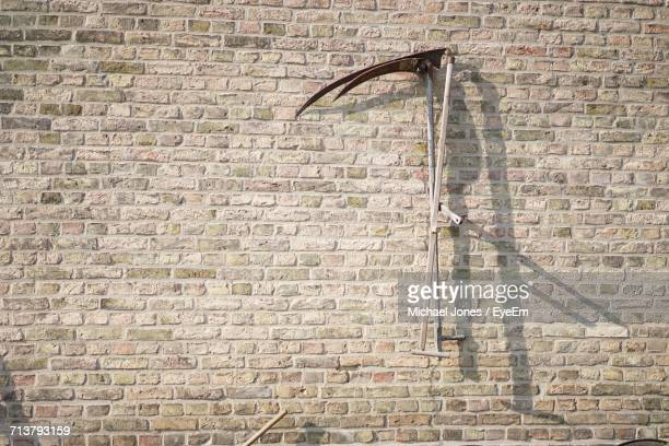 tools haning on brick wall - scythe stock photos and pictures