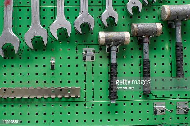 Tools hung neatly on a green peg board
