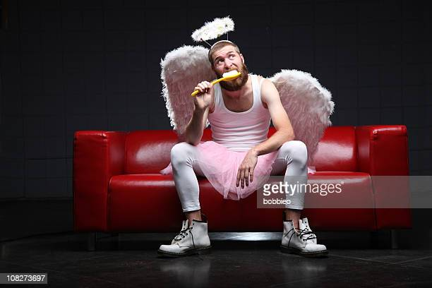 tooth fairy: brushing teeth with giant toothbrush - male angel stock photos and pictures