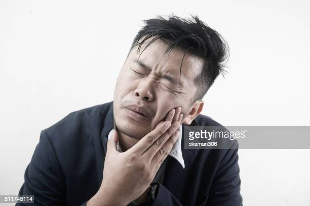 Toothache. Frustrated asian business man touching his cheek and eyes closed and feeling pain