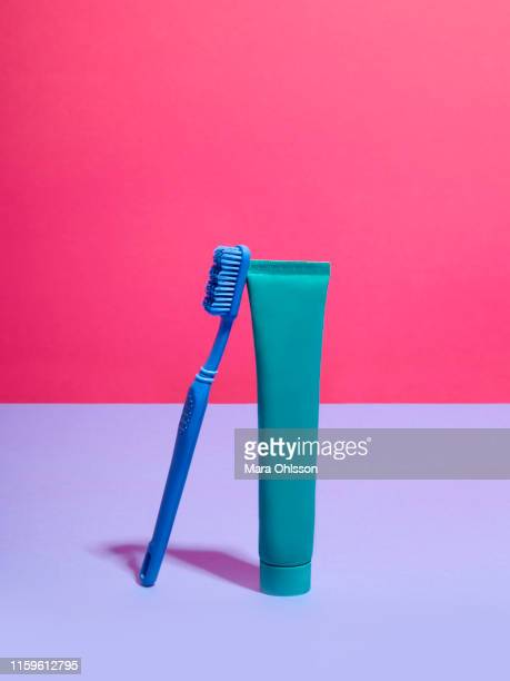 toothbrush and toothpaste against pink and lilac background - toothpaste stock pictures, royalty-free photos & images