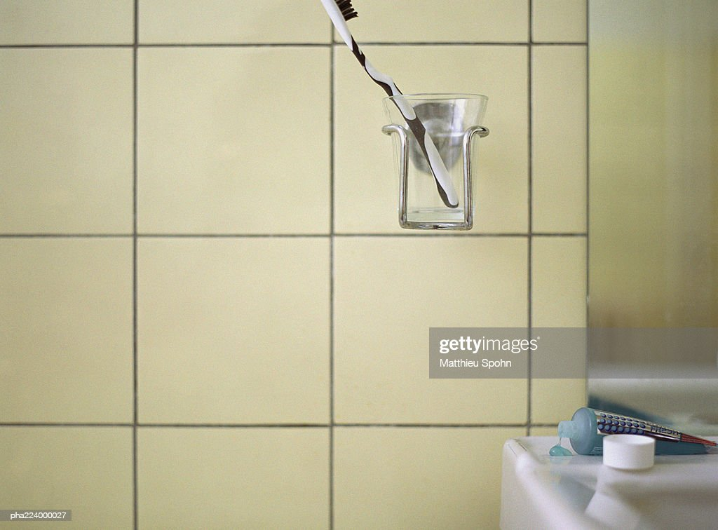 Toothbrush in cup holder next to bathroom sink. : Stockfoto