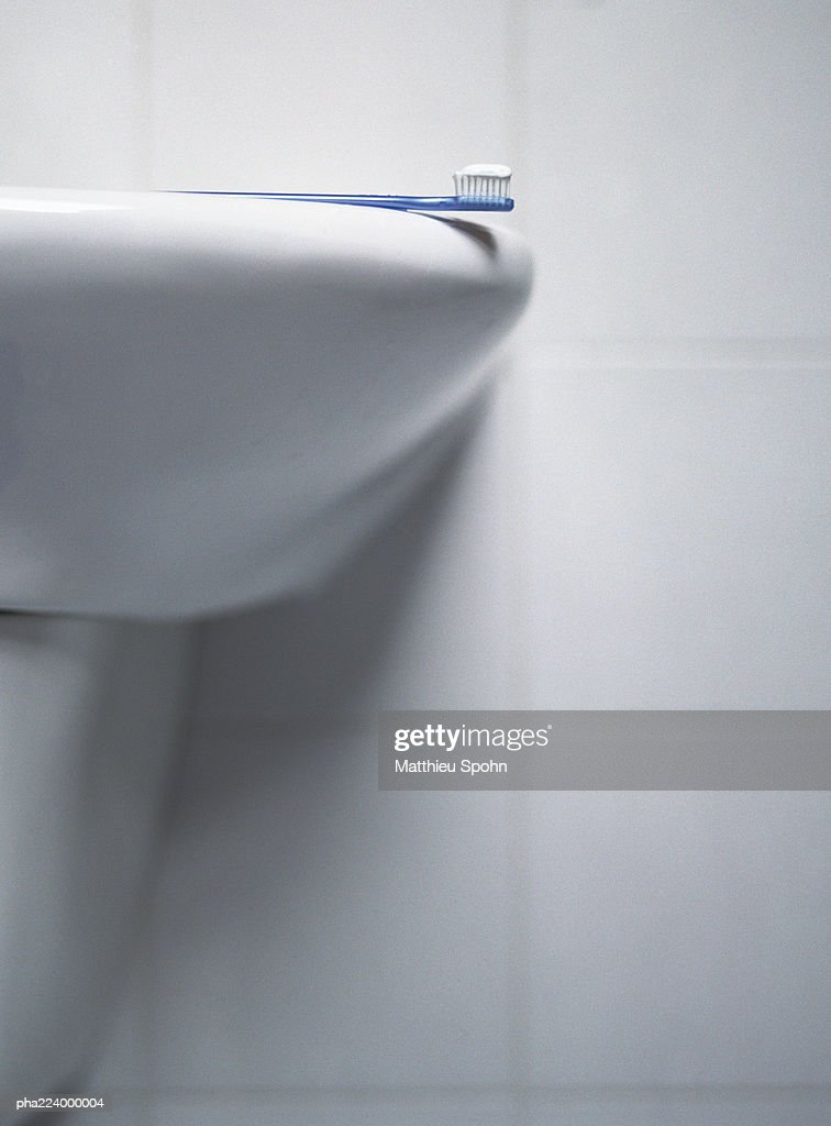 Toothbrush laying on sink, partial view. : Stockfoto