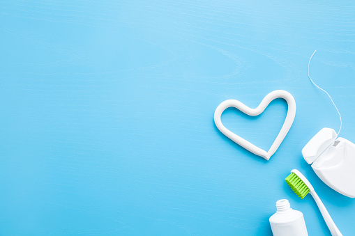 Toothbrush, white tube of toothpaste, container of dental floss on pastel blue background. Heart shape created from paste. Love healthy teeth concept. Empty place for text, quote, sayings or logo. 1133879113