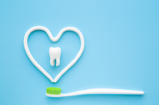 Toothbrush with green bristles on pastel blue background. Heart shape created from paste. White tooth in middle of heart. Love healthy teeth. Empty place for text, quote, sayings or logo. Closeup. 1143929500