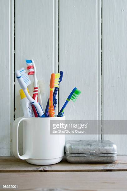 Toothbrushes in mug on shelf