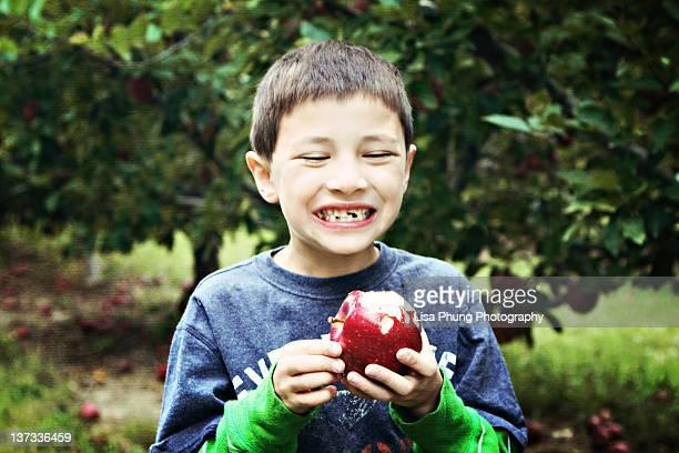 Toothless boy biting apple