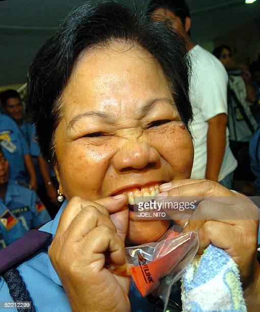 A toothless traffic officer installs a free denture given to her by President Gloria Arroyo's husband Jose Miguel Arroyo during a charity project in...