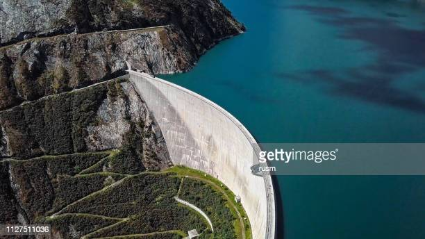 top aerial view of kolnbrein dam and malta road on kolnbreinspeicher lake in carinthia, austria. - hydroelectric power stock pictures, royalty-free photos & images