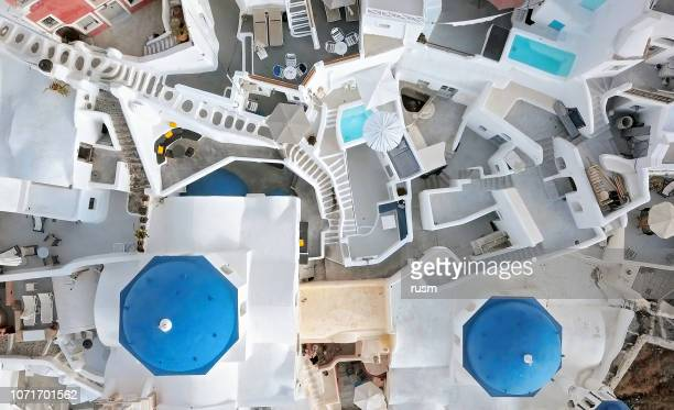 top aerial view of three blue domes church in oia town on santorini island, greece - santorini stock pictures, royalty-free photos & images