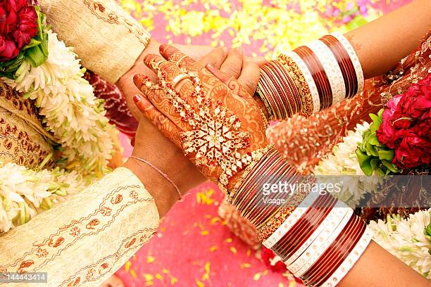 Top angle shot of Bride and groom holding each others hands
