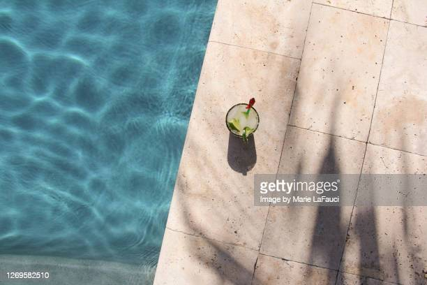 top angle view of a cocktail on the edge of a swimming pool - gulf coast states stock pictures, royalty-free photos & images