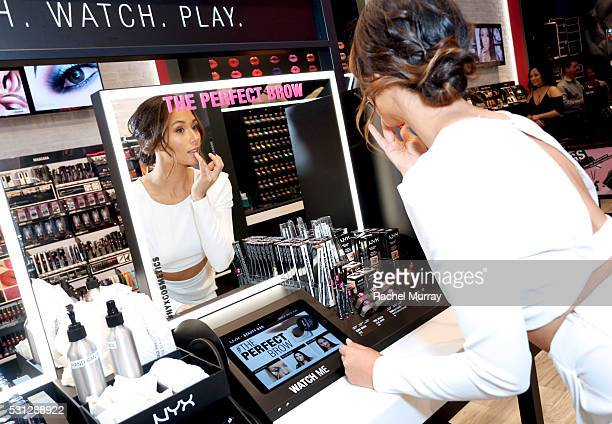 Top Beauty Influencer Aja Dang @ajadang trys out lip shades at the NYX Beauty Bar during the NYX Professional makeup store grand opening ribbon...