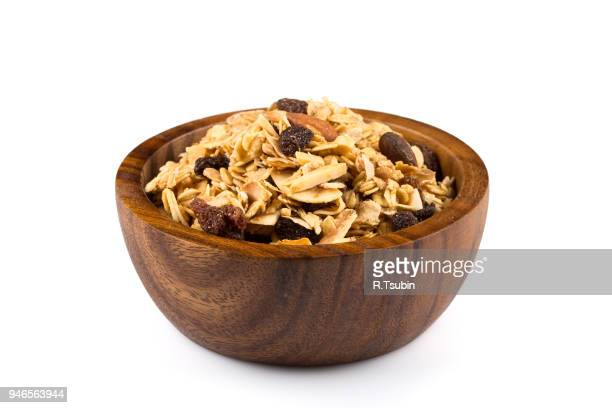 top close view of a dry mix of fruit and almond nuts cereal in a wooden bowl - 深皿 ストックフォトと画像