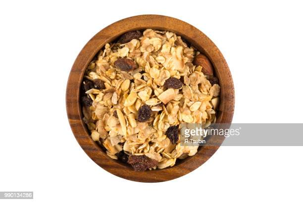 Top close view of a dry mix of fruit and almond nuts cereal in a wooden bowl