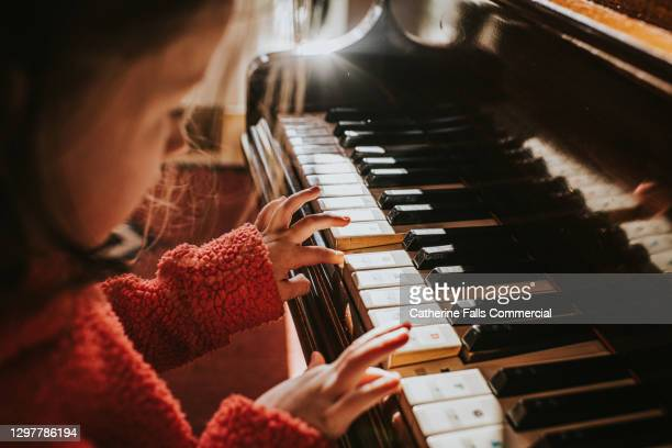 top down image of a little girl playing a grand piano - human finger stock pictures, royalty-free photos & images
