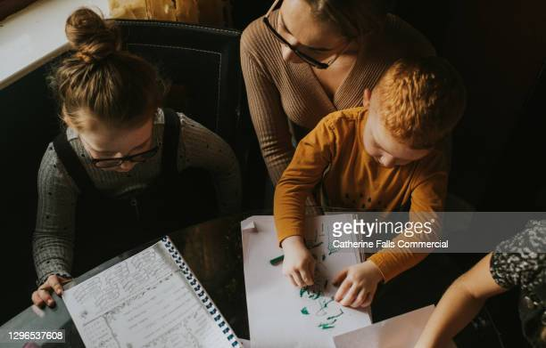top down image of mother homeschooling her children - inconvenience stock pictures, royalty-free photos & images