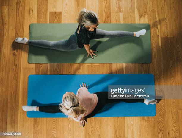 top down image of two woman on yoga mats doing the splits - elevated view stock pictures, royalty-free photos & images