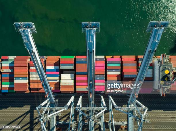 top down shot of container cranes over newly arrived cargo ship - long beach california stock photos and pictures
