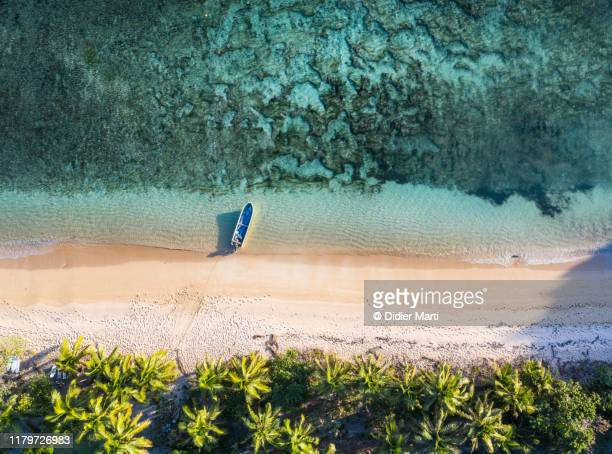 top down view of an idyllic island with a boat a coral reef in fiji in the south pacific ocean - fiji stock pictures, royalty-free photos & images