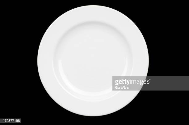 Top down view of empty white dinner plate on black surface