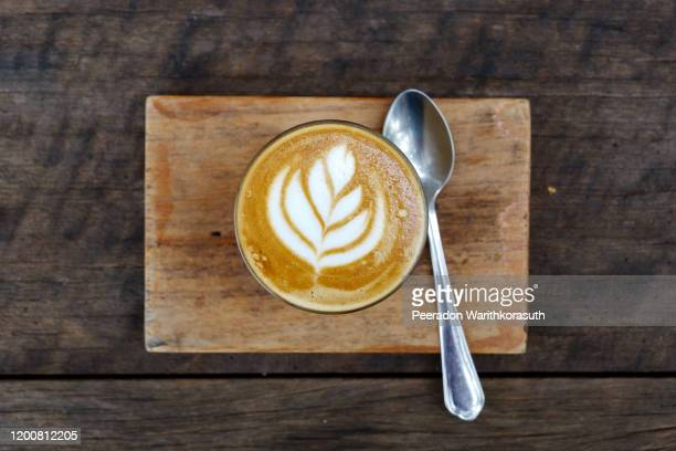 top flat view view at one cup of cappuccino or latte with flower pattern of latte art in transparent glass on wooden tray and table. hipster vibes and vintage tone. - high section stock pictures, royalty-free photos & images