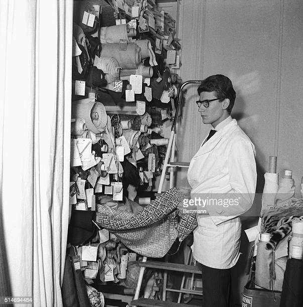 Top French fashion designer Yves Saint Laurent selects fabrics from the bolts in his Paris studio