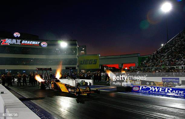 Top fuel dragsters light up as the leave the line during second round qualifying for the NHRA Carolinas Nationals at the Zmax Dragway on September 12...