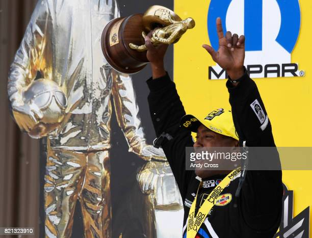 NHRA top fuel driver Antron Brown celebrates with fans after winning the 38th annual NHRA Mopar Mile High Nationals at Bandimere Speedway July 23 2017