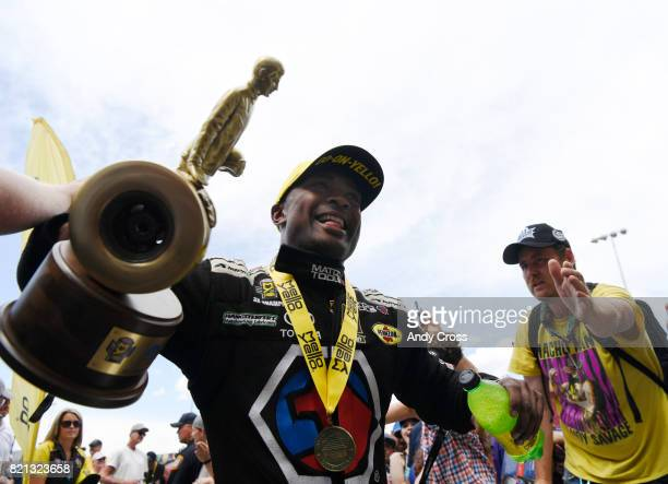 NHRA top fuel driver Antron Brown celebrates with fans on his way up to the stage after winning the 38th annual NHRA Mopar Mile High Nationals at...