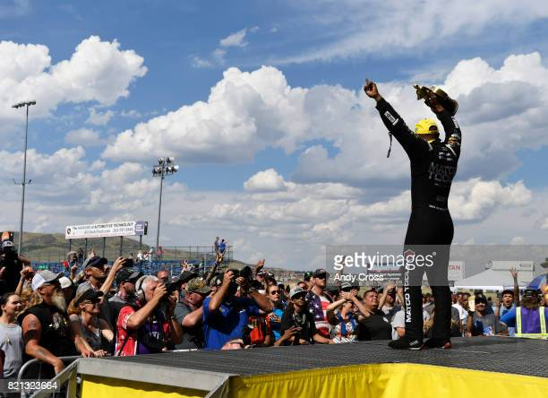 NHRA top fuel driver Antron Brown celebrates with fans on stage after winning the 38th annual NHRA Mopar Mile High Nationals at Bandimere Speedway...
