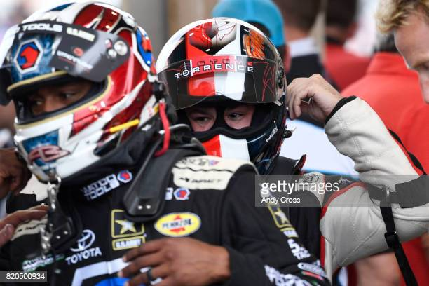 Top Fuel driver Steve Torrence right unbuckles his helmet during a rain delay as fellow driver Antron Brown does the same at the 38th annual Mopar...