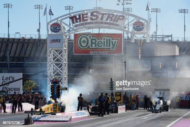 Top Fuel drivers Leah Pritchett, left, and Brittany Force smoke their tires before a run at the NHRA Toyota Nationals Sunday, October 29 at The Strip...
