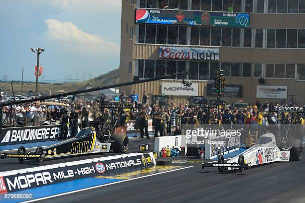 Top Fuel drivers Tony Schumacher and Antron Brown head down the track in the finals during day three of the NHRA Mile High Nationals at Bandimere...
