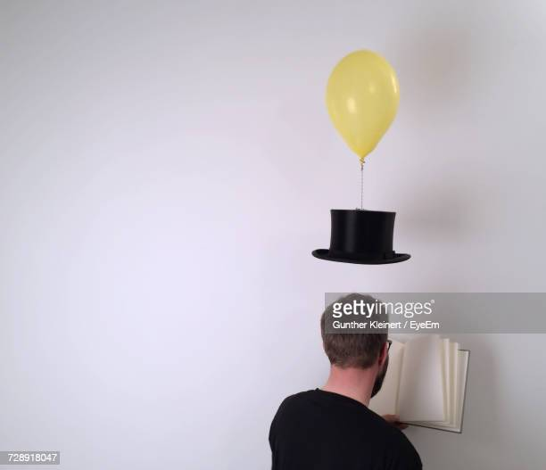 Top Hat Hanging From Helium Balloon Over Man Reading Book Against White Background