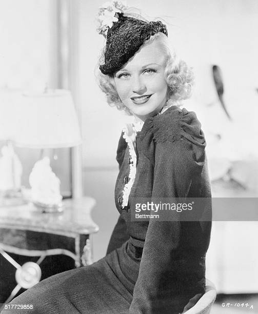 A top knot of multicolored pastel flowers is perched atop Ginger Rogers' peaked black lace straw hat designed by Lily Dache A wisp of veil covers the...