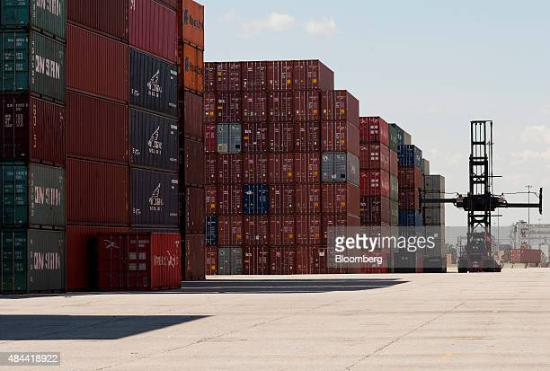 A top loader drives past a row of stacked shipping containers at the Port of Savannah in Savannah Georgia US on Friday Aug 14 2015 The trade deficit...