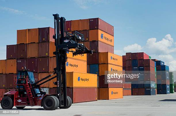Top loader passes a row of shipping containers stacked at the Port of Savannah in Savannah, Georgia, U.S., on Friday, Aug. 14, 2015. The trade...
