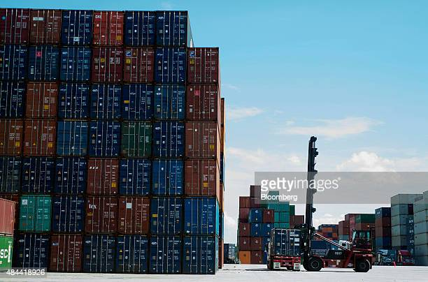 Top loader prepares to stack a shipping container at the Port of Savannah in Savannah, Georgia, U.S., on Friday, Aug. 14, 2015. The trade deficit in...