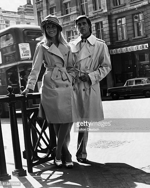Top London models wear raincoats from the 1974 spring collection of the classical clothing company, Burberry's. The woman models Glenco while the man...