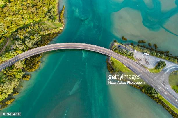 top looking down at bridge over waiwera river. - brücke stock-fotos und bilder