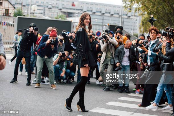 Top model Cat McNeil is surrounded by photographers and wears an all black outfit including a militarystyle sweater short skirt and knee high boots...