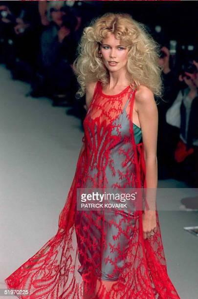 Top model Claudia Schiffer wears a transparent crimson smock with embroidered fern-leaf filligree over a pearl-gray satin slip-dress designed by Karl...