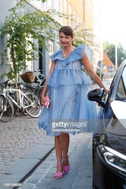 Top model Helena Christensen wearing a blue dress by Ganni, pink sandals and a red-white bag by Henrik Vibskov seen at Copenhagen Fashion Week...