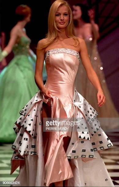 Top model Karen Mulder wears a cocktail dress in the Versace Atelier 'Couture Style' based on fluid fabrics and pearly icepastels marked with bold...