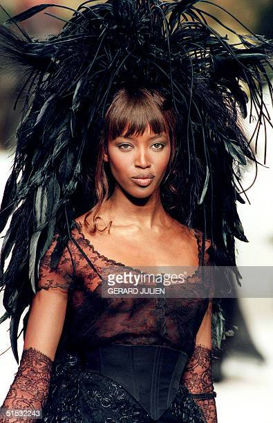 Top model Naomi Campbell displays a short lace dress worn with a hat made of feathers during the presentation of Chanel's 1994 Spring/Summer haute...