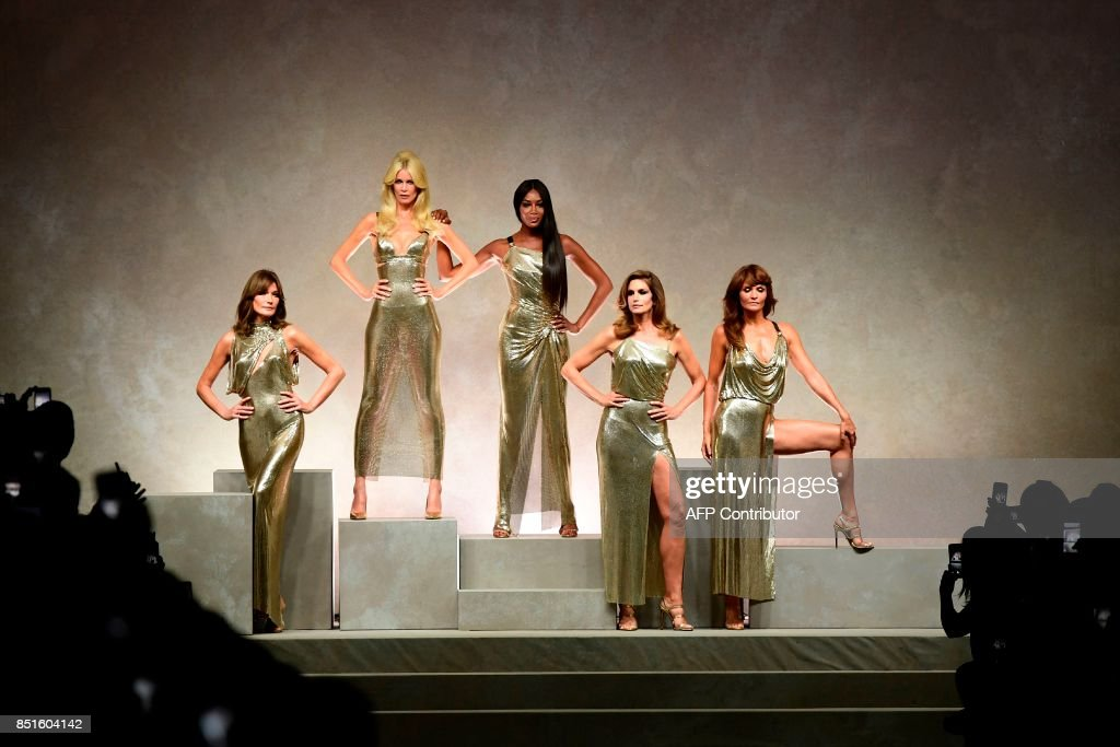 Top models (from left) Carla Bruni, Claudia Schiffer, Naomi Campbell, Cindy Crawford and Helena Christensen pose at the end of the show for fashion house Versace during the Women's Spring/Summer 2018 fashion shows in Milan, on September 22, 2017. / AFP PHOTO / Miguel MEDINA