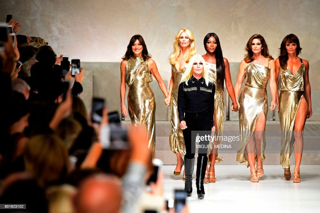Top models (from left) Carla Bruni, Claudia Schiffer, Naomi Campbell, Cindy Crawford and Helena Christensen pose with Italian designer Donatella Versace (C) at the end of the show for fashion house Versace during the Women's Spring/Summer 2018 fashion shows in Milan, on September 22, 2017. The Spring 2018 show was a tribute to mark the 20th anniversary of the murder of Italian designer Gianni Versace. Donatella Versace, who took over as designer soon after her brothers sudden death, presented a blockbuster tribute show that ended with five of the original supermodels taking to the catwalk together, soundtracked by George Michaels Freedom. / AFP PHOTO / Miguel MEDINA