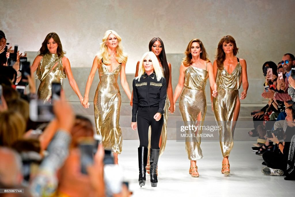 Top models (from left) Carla Bruni, Claudia Schiffer, Naomi Campbell, Cindy Crawford and Helena Christensen walk the runway with Italian designer Donatella Versace (C) at the end of the show for fashion house Versace during the Women's Spring/Summer 2018 fashion shows in Milan, on September 22, 2017. The Spring 2018 show was a tribute to mark the 20th anniversary of the murder of Italian designer Gianni Versace. Donatella Versace, who took over as designer soon after her brothers sudden death, presented a blockbuster tribute show that ended with five of the original supermodels taking to the catwalk together, soundtracked by George Michaels Freedom. / AFP PHOTO / Miguel MEDINA