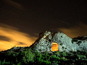 Top of a mountain with an ancient refuge excavated in the rock, a night of sky with clouds orange color and with stars
